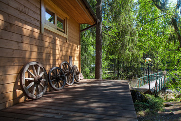 Wooden house in the forest with old wheels from the cart
