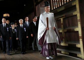 A group of lawmakers including Japan's ruling Liberal Democratic Party lawmaker Hidehisa Otsuji are led by a shinto priet as they offer prayers for the war dead at the Yasukuni Shrine in Tokyo