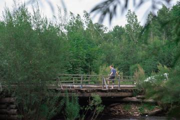 Man sitting on the wooden bridge railings on bridge over the small village river