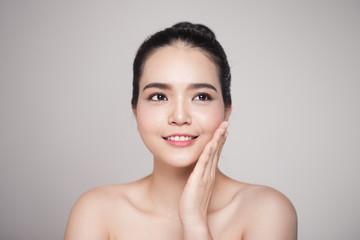 Happy smiling beautiful asian woman touching her face.