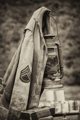 Sepia photograph of a US army sergeant jacket from WW2 hanging on a later in an upright vertical format