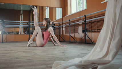 Young pretty girl demonstrates the flexibility of her body