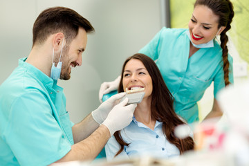 Dentist checking and selecting color of young woman's teeth