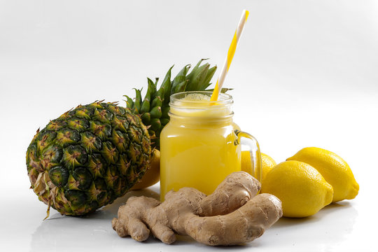 Juicing raw fruits and vegetables and juice extractor recipes concept with pineapple, lemon and ginger, the ingredients for a detox smoothie that helps with inflammation and digestion