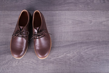Brown leather men's shoes on wood background