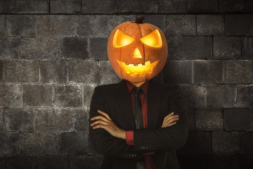 Young halloween man wearing suit with pumpkin head