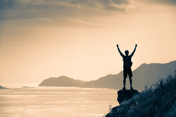 Victory, winning, adventure, goals concept. Man standing on mountain with arms in the air celebrating.
