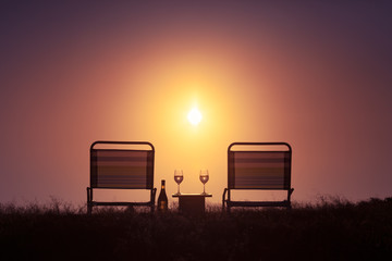 Romantic outdoor nature setting. Pair of chairs and  wine glasses against a beautiful sunset.