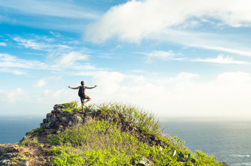 Man on a mountain striking a balance yoga pose feeling at peace with nature.