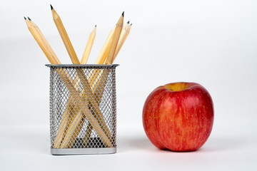 pencils in basket with apple on white, back to school concept