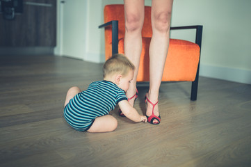 Little baby playing with mother's fancy shoes