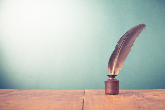 Vintage old quill pen with inkwell on wooden table. Retro style filtered photo