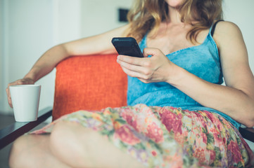 Young woman with cup and smart phone at home