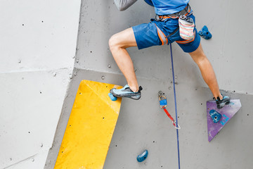 Foot of a sportsman climber on artificial boulder gym wall. Close-up view