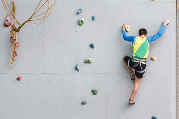 Young Man Climbs Up An Artificial Rock Wall, sport and fitness concept