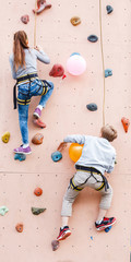 Two children climb the bouldering artificial wall and compete in speed and strength
