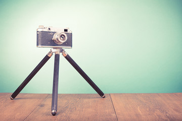 Retro old outdated rangefinder film camera with tripod from 50s on table front mint green background. Vintage style filtered photo