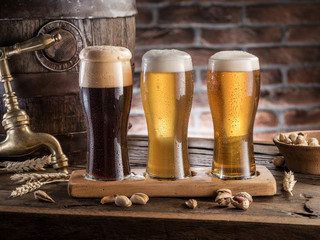 Wall Mural - Glasses of beer and ale barrel on the wooden table. Craft brewery.