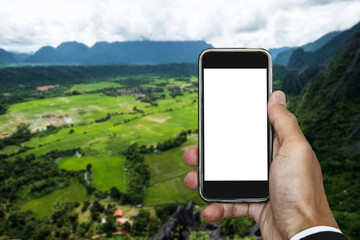 Hand holding smart phone, on the mountain beautiful nature view, empty white screen for copy space