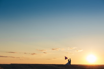 Bride and groom in a field at sunset with balloon