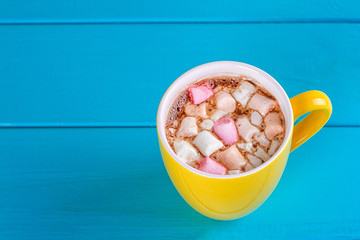 Yellow cup of hot cocoa with marshmallows
