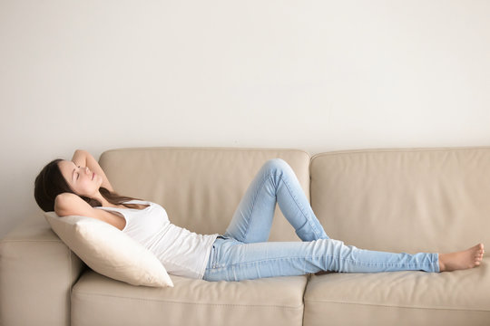 Young woman lying on couch cushion with eyes closed, relaxing on cozy sofa pillow, relaxed girl taking nap at home hands behind head, breathing fresh air, no stress, enjoying day off in living room