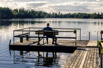 Portrait of young and attractive man in suit sitting on a bench on pier next to the huge lake and enjoying the view.
