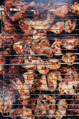 Pieces of chicken cooking on metal grill