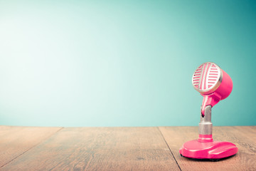 Retro old microphone from 60s front mint green background. Vintage style filtered photo