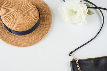 straw hat with peony and black handbag on the white table