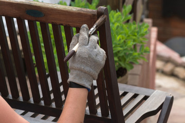 Woman hand with brush restored wooden furniture