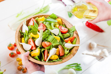 man pouring olive oil into healthy salad on kitchen
