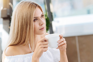 Thoughtful young woman drinking tea