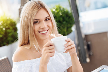 Delighted happy woman enjoying her drink