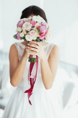 Bride holds tender pink bouquet