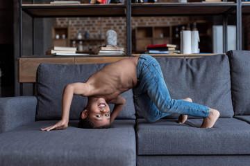 shirtless little kid playing on sofa