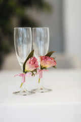Champagne flutes decorated with roses stand on the table
