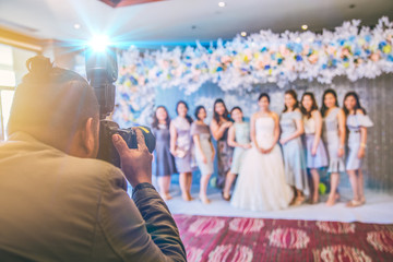 professional wedding asian photographer on duty take a photo group of bride and friends.