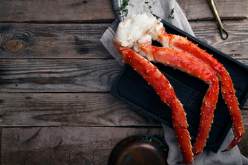 Fresh crab claws on black wooden tray on vintage wooden background. Horizontal composition. Copy space for banner.