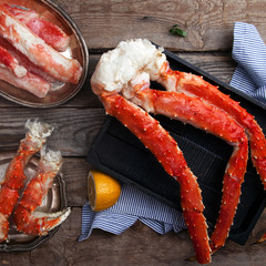 Fresh crab claws and different types of crab meat on black wooden tray on vintage wooden background with vintage plates and lemon slices. Square.