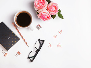 Coffee, pink roses and other small objects on the white background