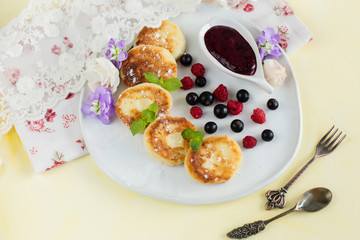 Cottage cheese pancakes on a plate with berries on yellow background