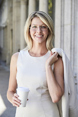 Beautiful woman with coffee and holding jacket, smiling