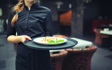 Waiters carrying plates with food, in a restaurant.