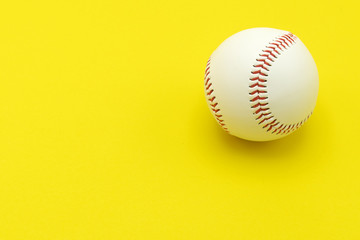 Isolated baseball on a yellow background and red stitching baseball. copy space.