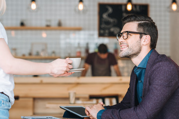 waitress with order for businessman in cafe