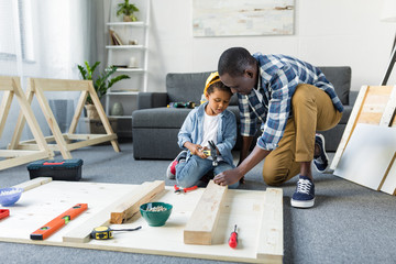 adorable african-american father and son doing renovation
