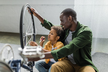 happy african-american father and son repairing bicycle