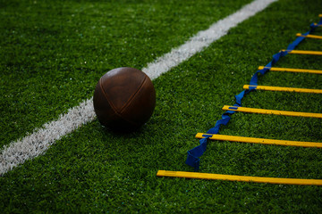 Photo of an American football on a grass next to the touchline, shot from above.