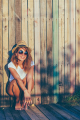 Summertime portrait of young woman by the fence
